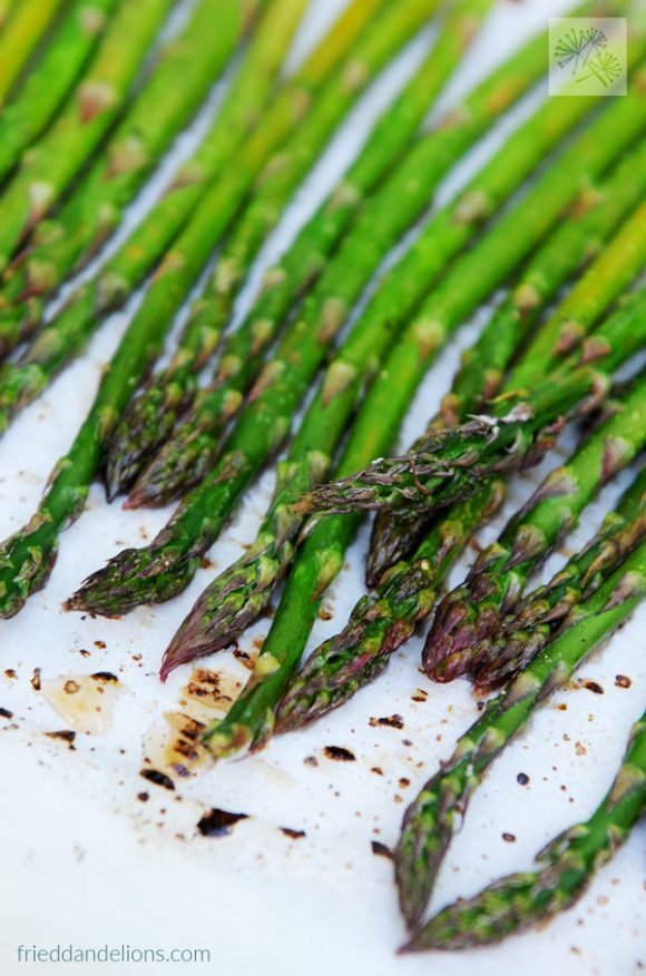 roasted asparagus with lemon after it is cooked, on a baking sheet lined with parchment