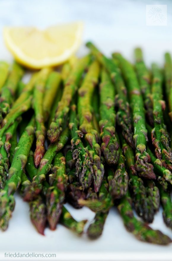close up view of roasted asparagus with lemon