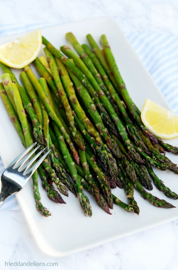 plate of roasted asparagus with lemon with lemon wedges on the plate