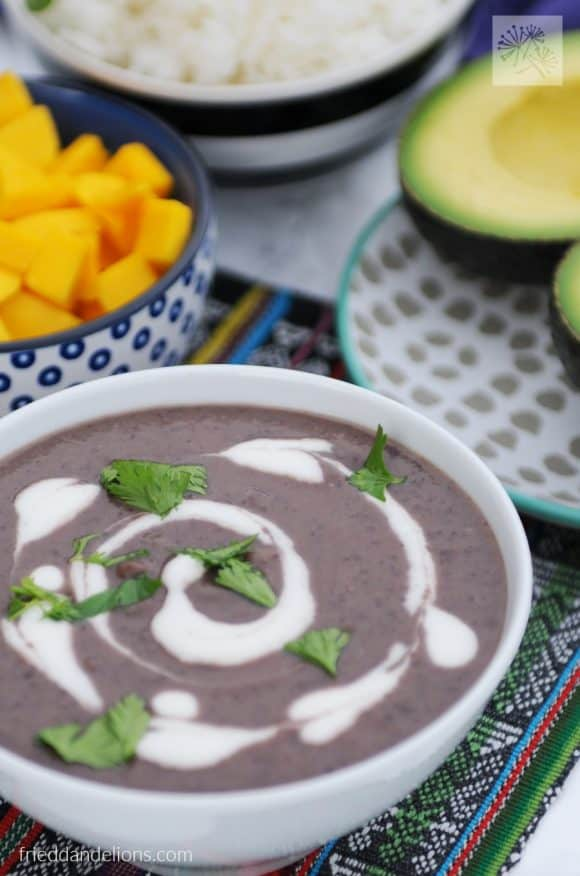 close up of bowl of black bean soup with mangoes, avocado, and white rice in the background