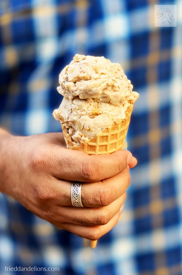 man holding Maple Bacon Ice Cream cone with silver ring and blue plaid shirt in background