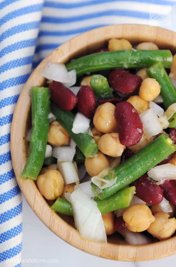 close up of wooden bowl with three bean salad, blue and white striped napkin