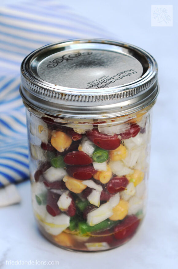 jar of three bean salad with blue and white striped napkin in background