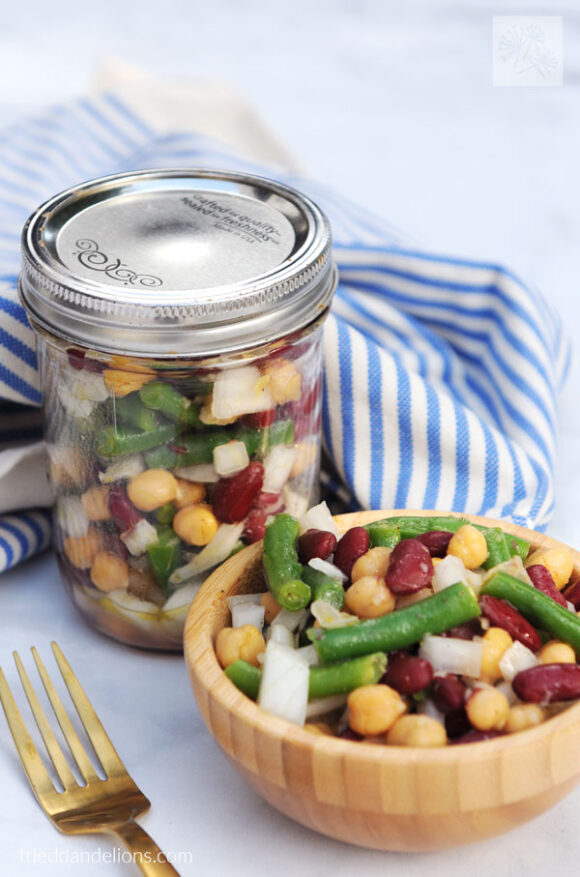wooden bowl of three bean salad, with jar full of three bean salad behind it, gold fork, blue and white striped napkin