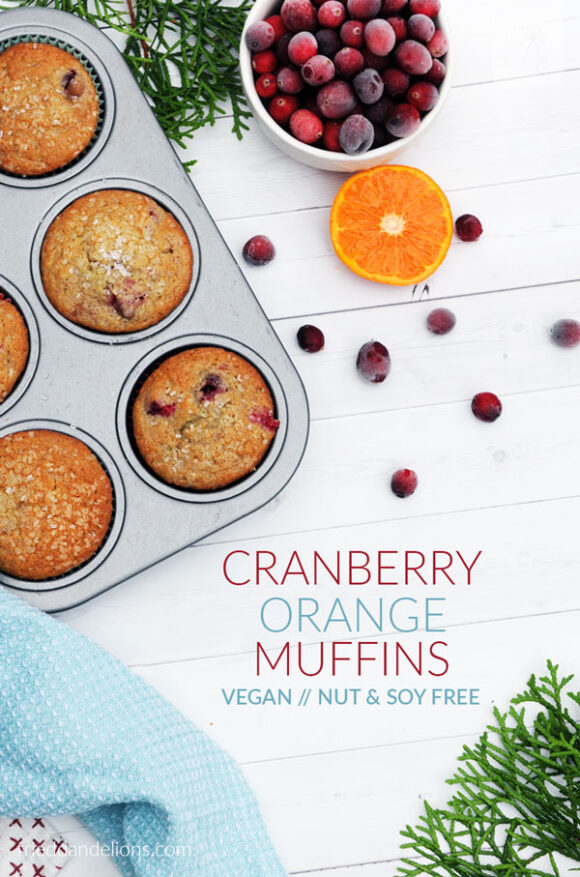 pan of vegan cranberry orange muffins with bowl of cranberries, sliced orange, evergreen branches, white background, and text overlay