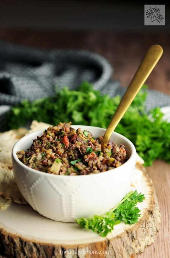 white bowl filled with olive tapenade with gold spoon
