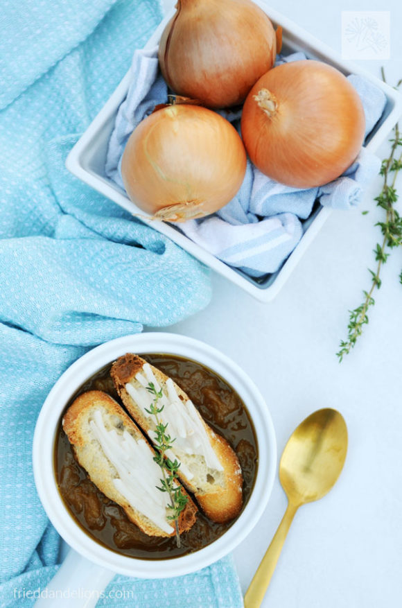 overhead view of vegan French Onion Soup with onions, gold spoon, sprig of thyme, and blue dish towel in background
