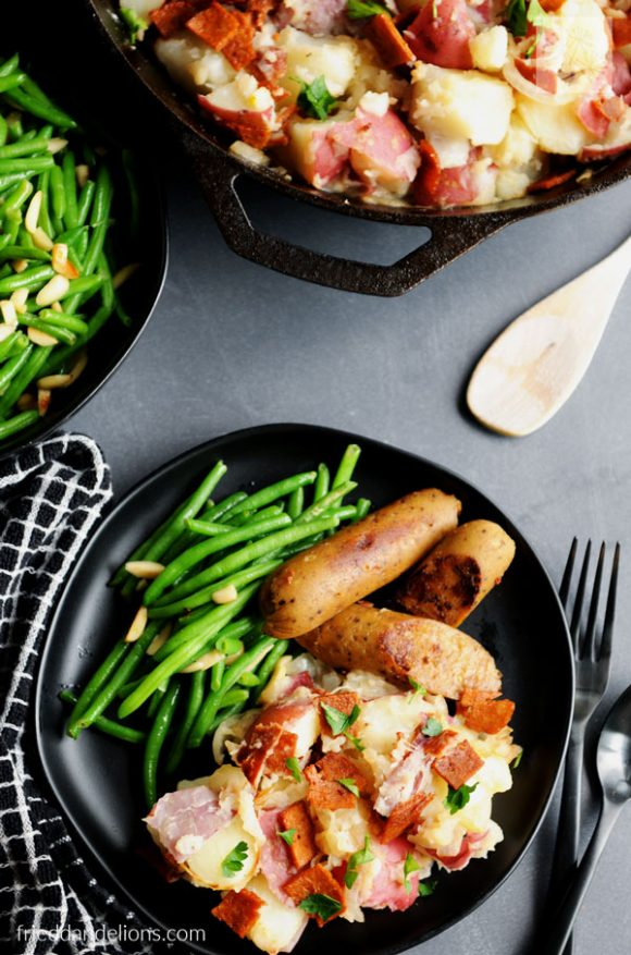 overhead of plate of Vegan German Potato Salad with vegan sausage, green beans, wooden spoon, black plates