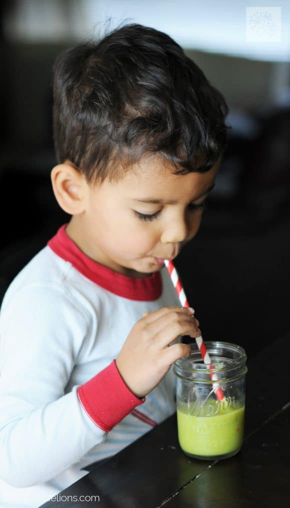 young boy sipping citrus explosion green smoothie from red and white straw