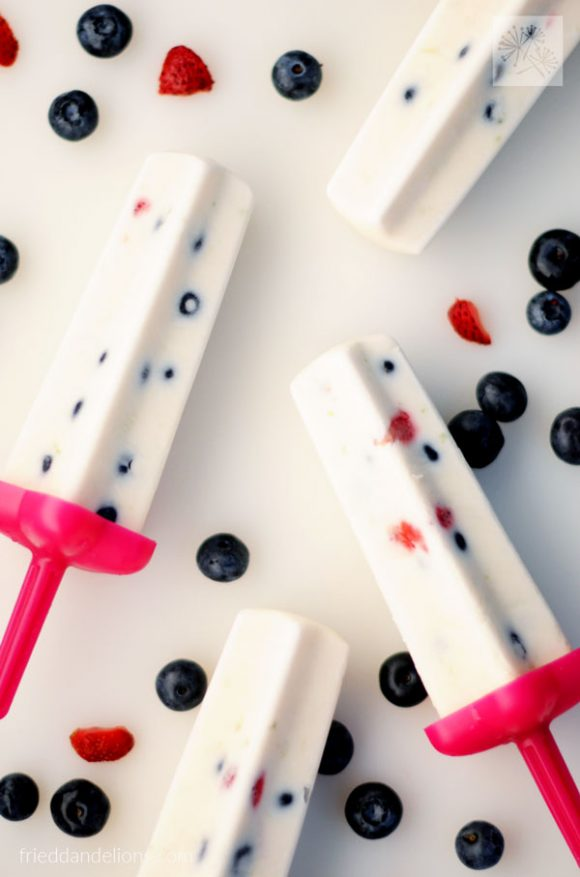 overhead shot of 4 Firecracker Popsicles with berries on a white background