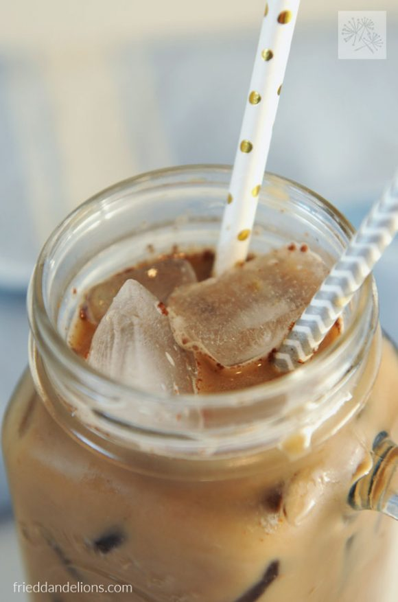 close up of cold brew coffee milk over ice with two straws