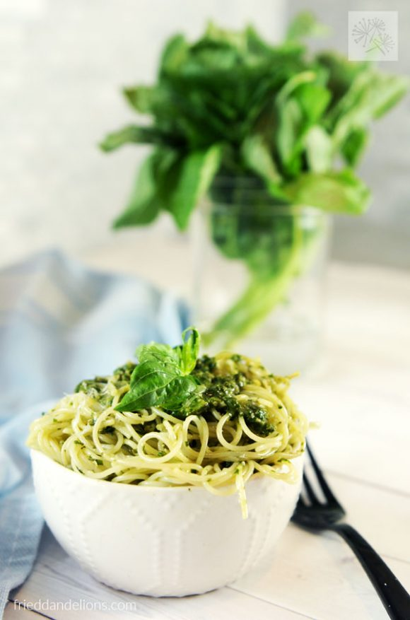close up bowl of Vegan Pesto with bundle of basil in background