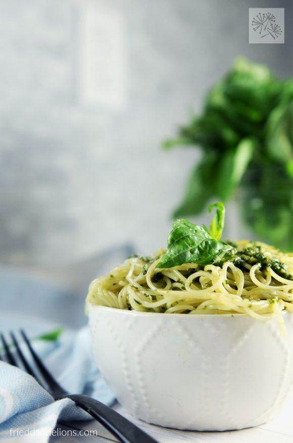 bowl of Vegan Pesto with bundle of basil in the background
