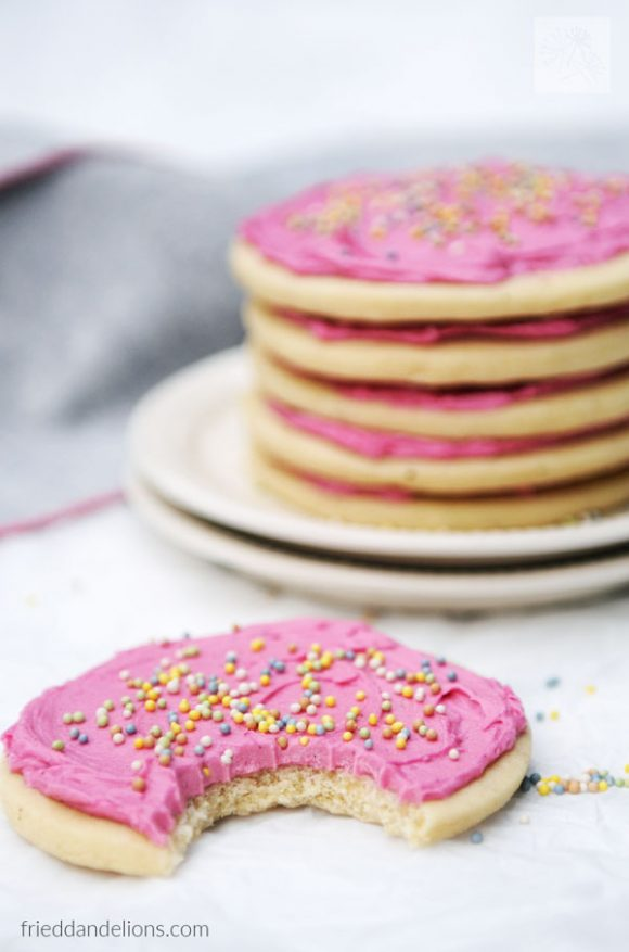 stack of Classic Vegan Sugar Cookies in background with close up of cookie with bite taken out in the foreground
