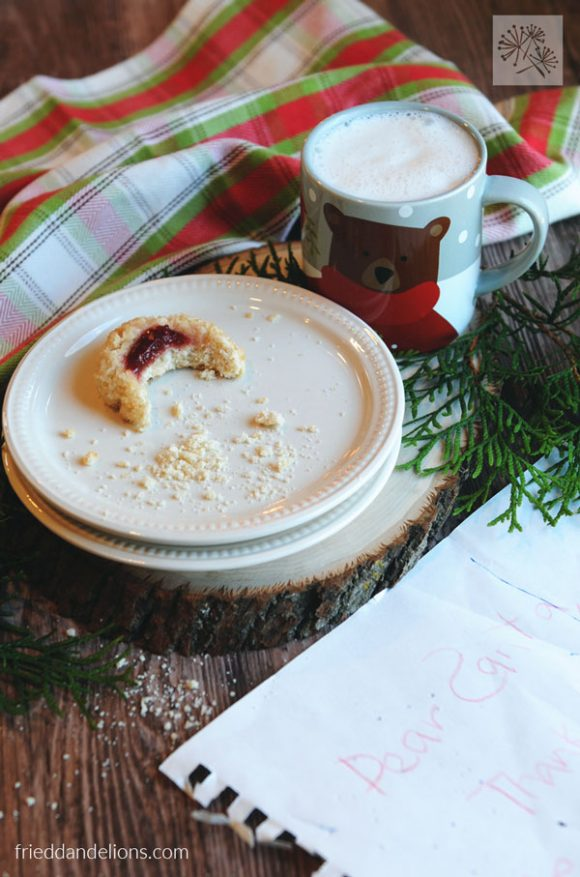 picture of partly eaten vegan thumbprint cookies with a mug of milk, plaid napkin, greenery, and note to Santa