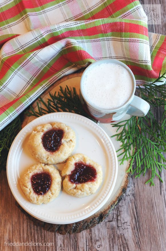 overhead view of vegan thumbprint cookies with plaid napkin, mug of milk, and greenery