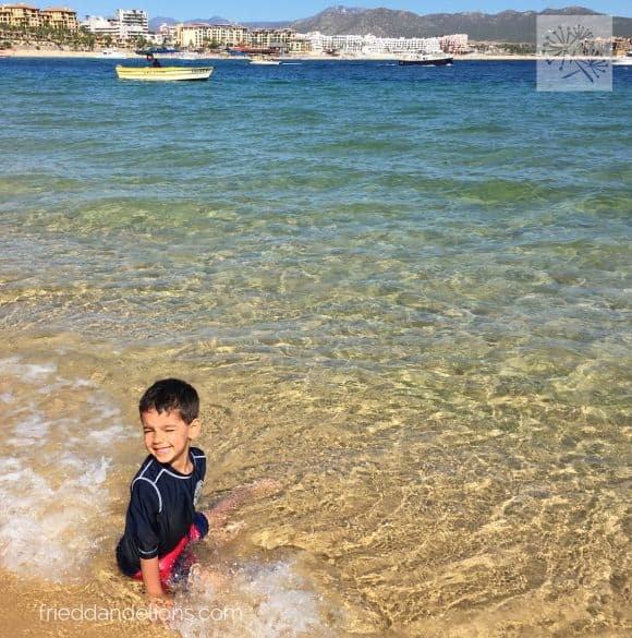 young boy playing at the beach in Cabo