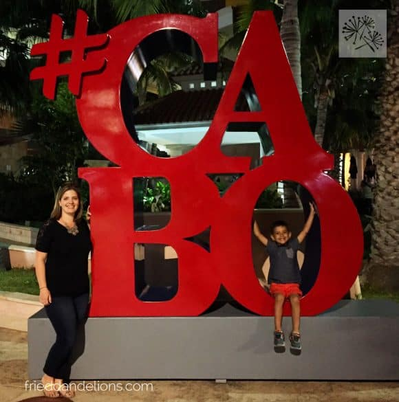 Sarah, of Fried Dandelions, and her son in front of the #Cabo sign