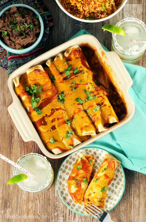baking dish full of jackfruit enchiladas with margaritas for vegan taco Tuesday