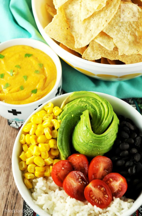 vegan nacho bowl with bowl of queso and chips in the background for vegan taco Tuesday