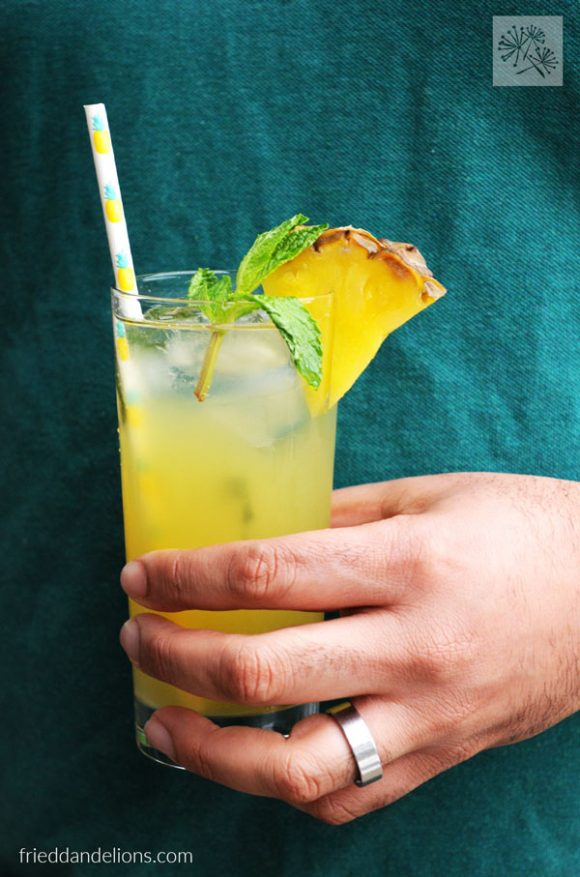 glass of pineapple mojito held in man's hand with green background for vegan taco Tuesday