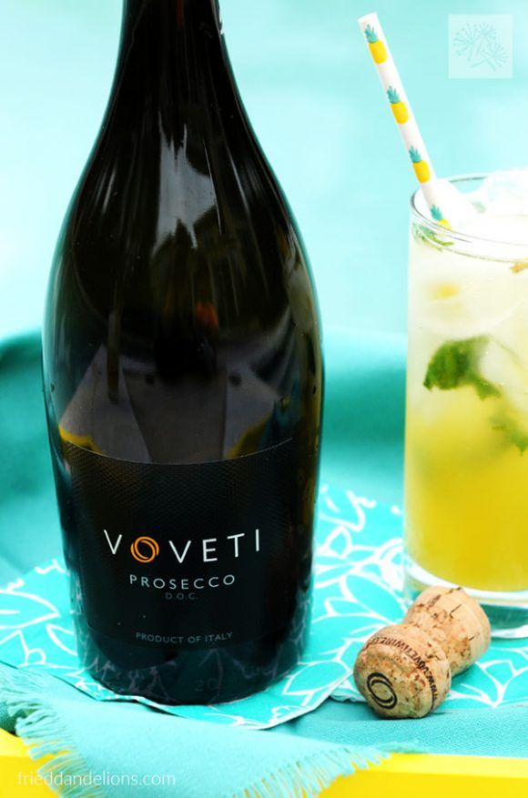 close up of Voveti prosecco with pineapple mojito behind it
