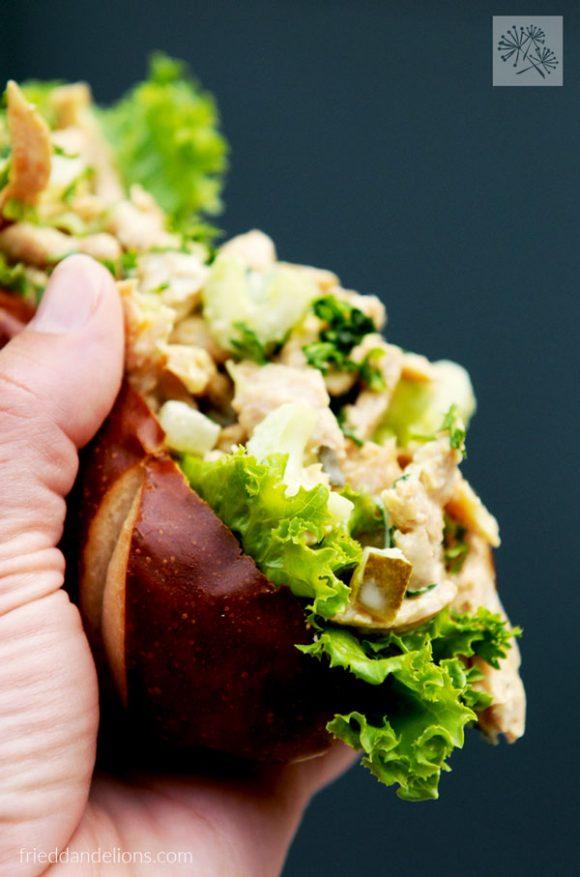 hand holding Vegan Chicken Salad with Pickles sandwich