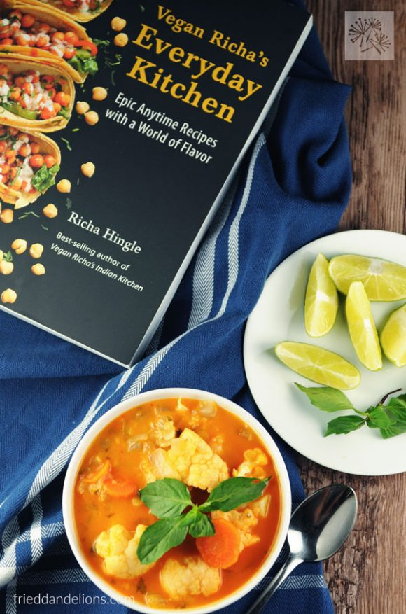 overhead view of Red Curry Soup with Lentils by Vegan Richa with cookbook and limes