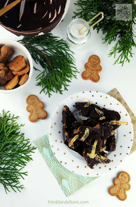spread of Gingerbread Chocolate Bark with evergreen branches and bowl of chocolate