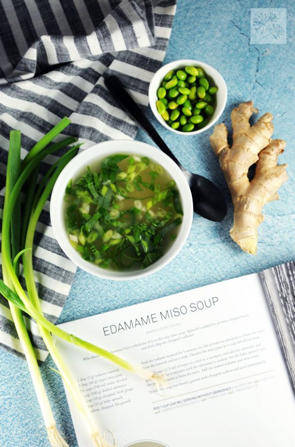 overhead shot of edamame miso soup with open copy of cookbook Awesome Vegan Soups