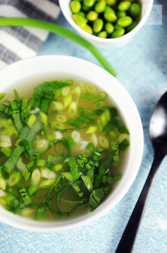 close up view of edamame miso soup with green onions