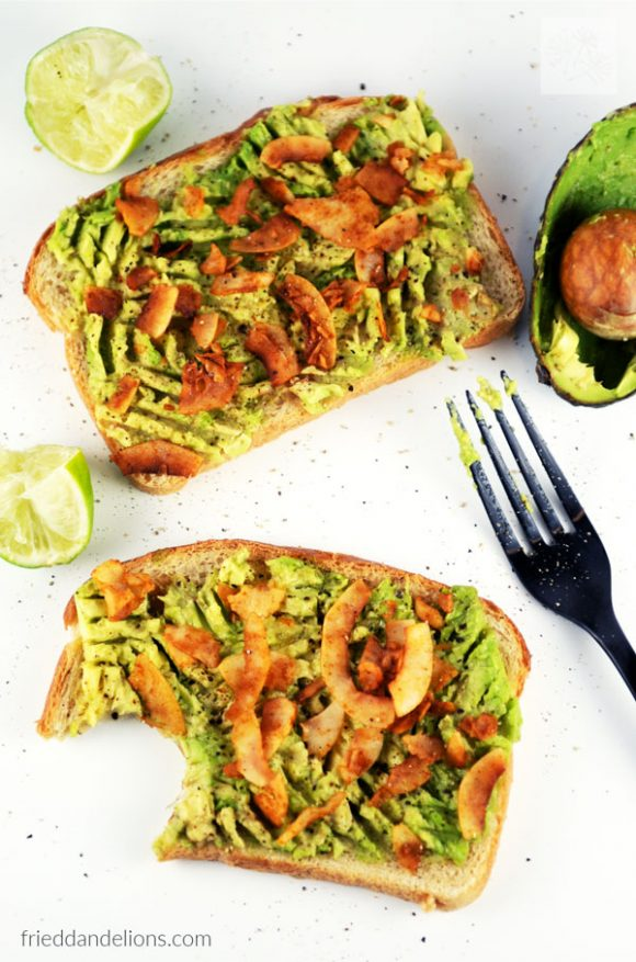overhead view of two pieces of avocado toast with coconut bacon with squeezed limes and avocado in background