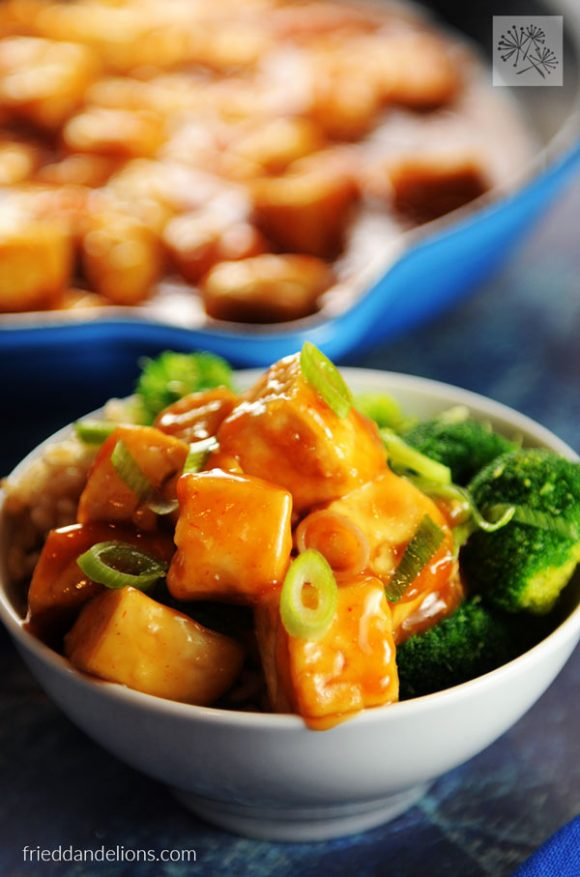 bowl of sweet and sour tofu with pan of tofu in background