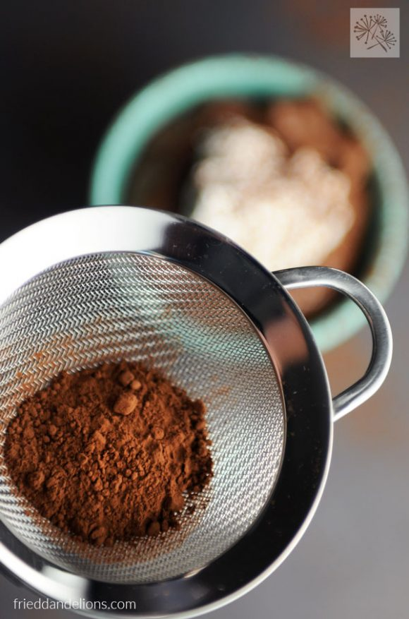 sifting cocoa powder over bowl of vegan chocolate mousse