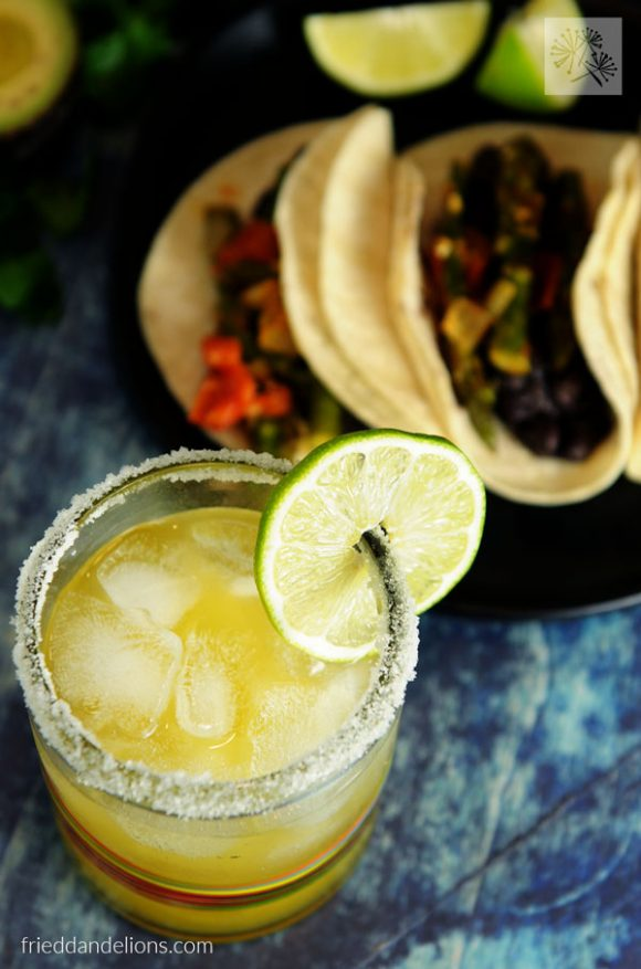 close up of margarita with braised asparagus tacos in background