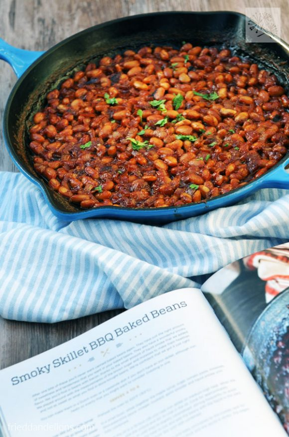 overhead of skillet with vegan baked beans with cookbook in front