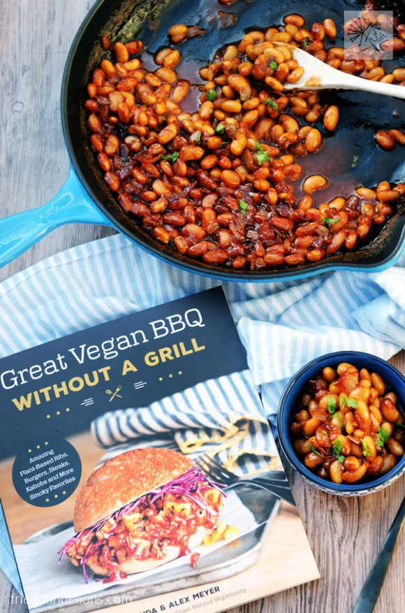 overhead of skillet with vegan baked beans with small dish of beans and cookbook in foreground