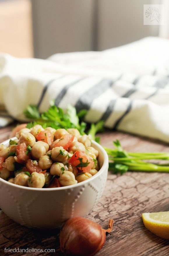 bowl of Chickpea Salad with Lemon and Shallots with black striped napkin in background