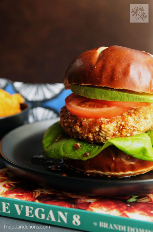 front view of teriyaki veggie burgers stacked on top of The Vegan 8 cookbook
