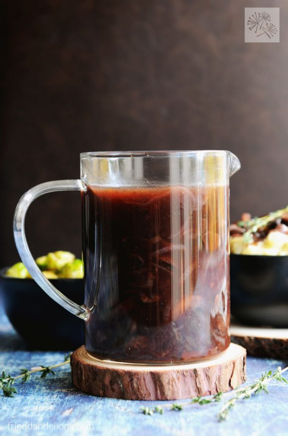 front shot of vegan red wine gravy in clear pitcher with brown background