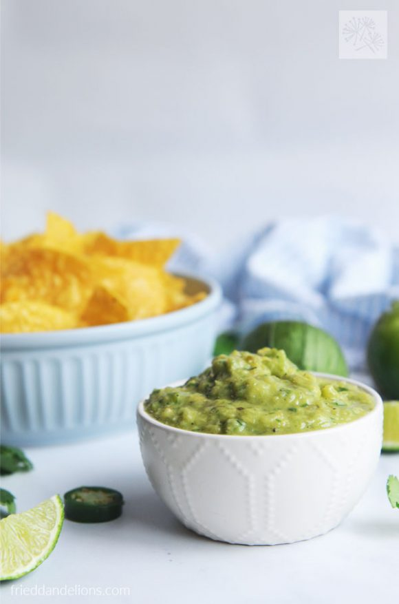 front shot of a white bowl of Charred Tomatillo Salsa Verde with Avocado with a light blue bowl or tortilla chips in the background