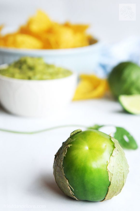 close up of tomatillo with a bowl of Charred Tomatillo Salsa Verde with Avocado and tortilla chips in the background