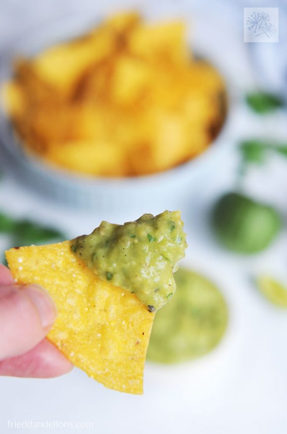 tortilla chip with Charred Tomatillo Salsa Verde with Avocado with a bowl of tortilla chips in the background