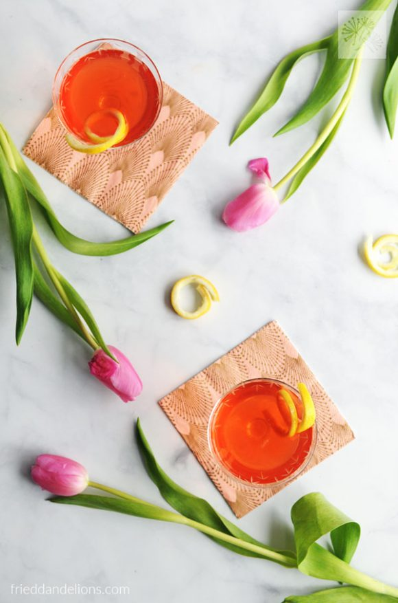overhead of two Rosé Vodka Cocktails with lemon twists and pink tulips strewn about
