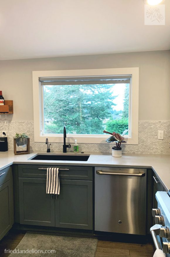 view of black quartz sink and stainless steel dishwasher in grey kitchen renovation