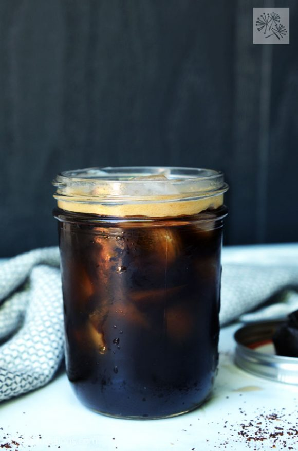 mason jar filled with dark coffee made with DIY Cold Brew Coffee Bags, grey dishtowel, black background
