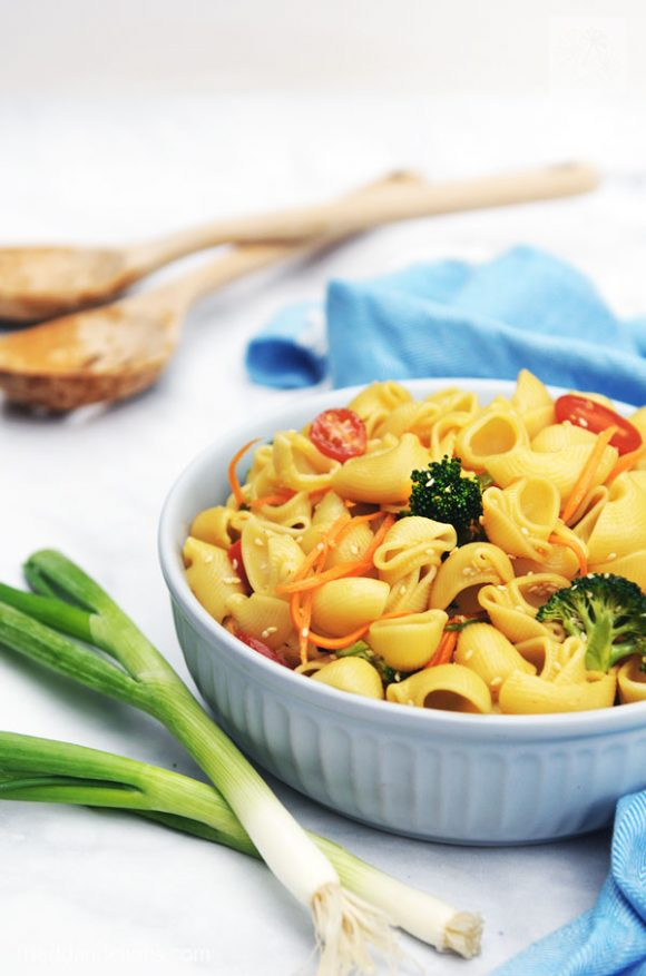 large bowl of pasta salad with green onions in foreground and blue napkin and wooden salad tongs in the background