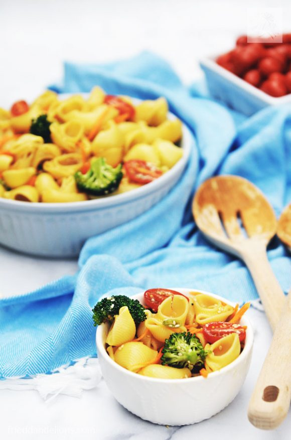 small bowl of pasta salad in foreground with large bowl of pasta salad, blue napkin, wooden salad tongs, and grape tomatoes in the background