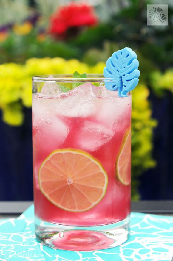 front view of a glass of Blueberry Mojito Punch with blue glass charm, lime slice in the glass, and blue and green outdoor background