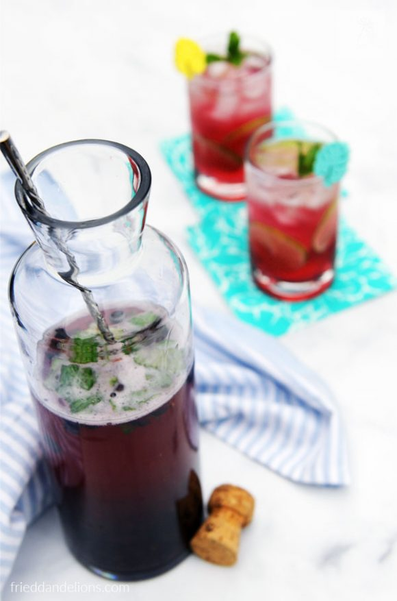 carafe of Blueberry Mojito Punch with two glasses in the background, white background, cork, blue and turquoise napkins
